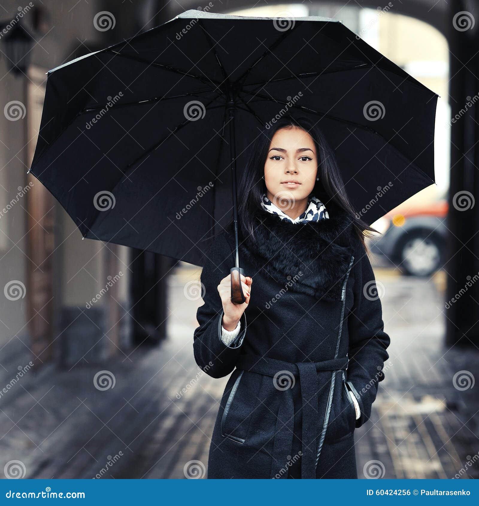 有伞的美丽的深色的女孩