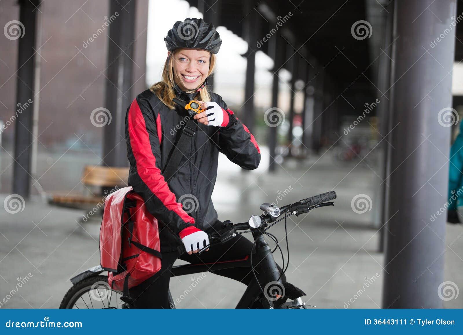 有传讯者袋子的女性骑自行车者使用