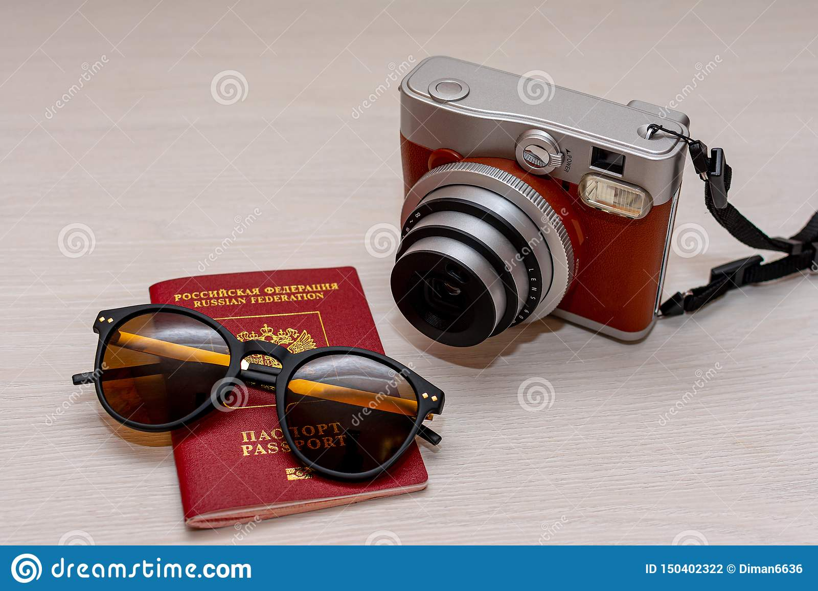 有俄罗斯联邦的公民的护照和一台立即照片照相机的太阳镜在白色木背景