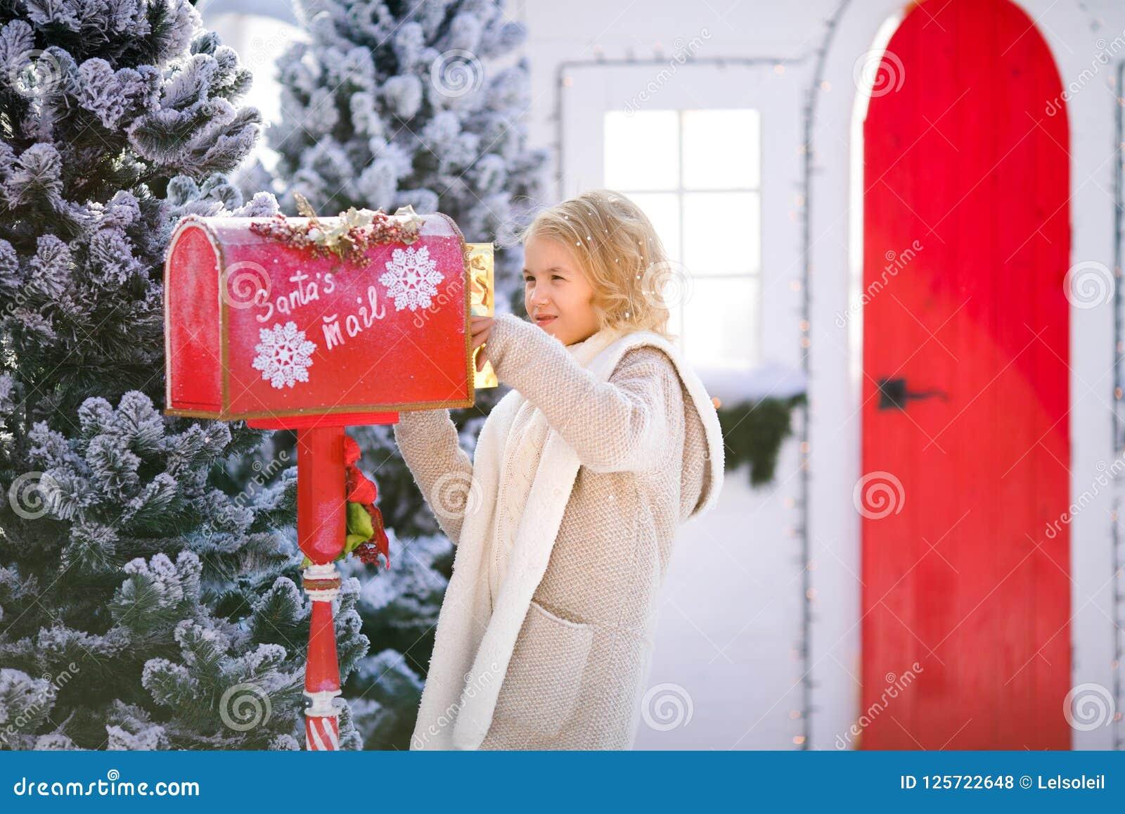 有信件的好白肤金发的卷曲女孩在圣诞老人` s邮箱附近