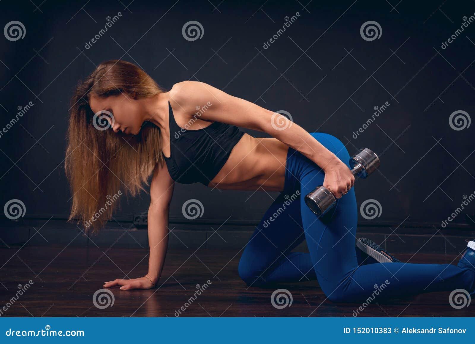 有做三头肌的哑铃的女孩锻炼在倾斜一只手的我的膝盖对地板延伸沿身体的胳膊