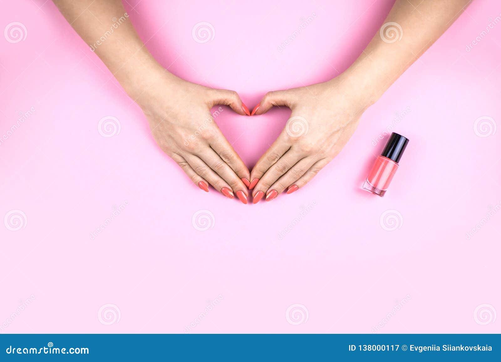 有做心脏的珊瑚修指甲的妇女的手