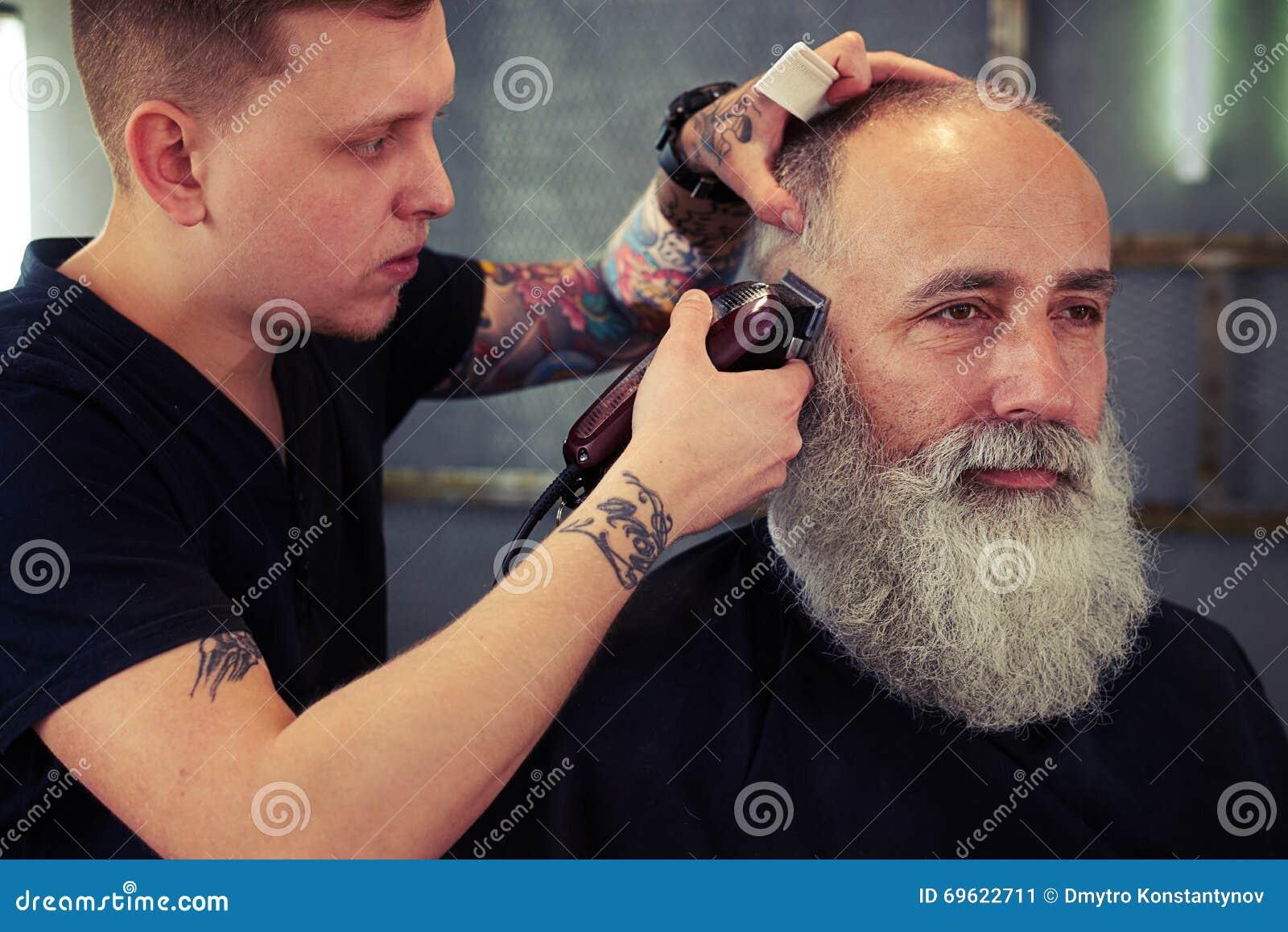 有纹身花刺的理发师做理发对有胡子的行家老人和与电剃刀一起使用.