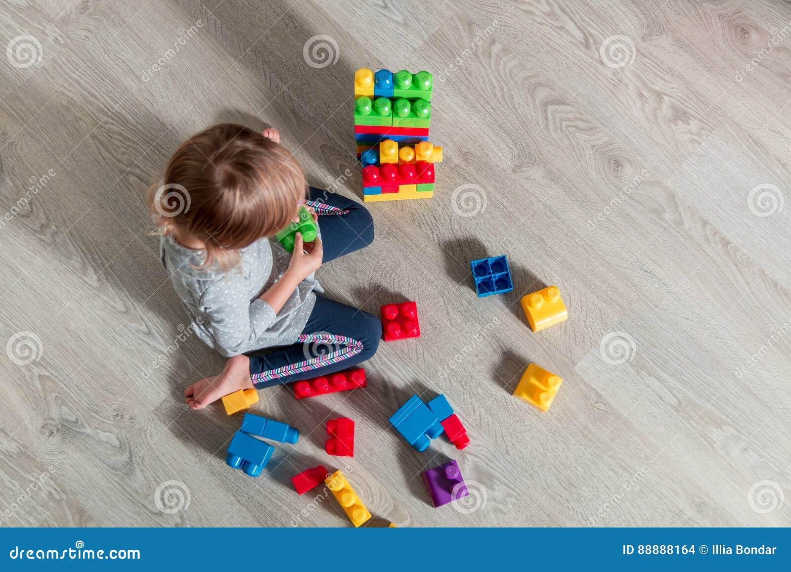 有儿童的女孩明亮的塑料建筑块乐趣和修造