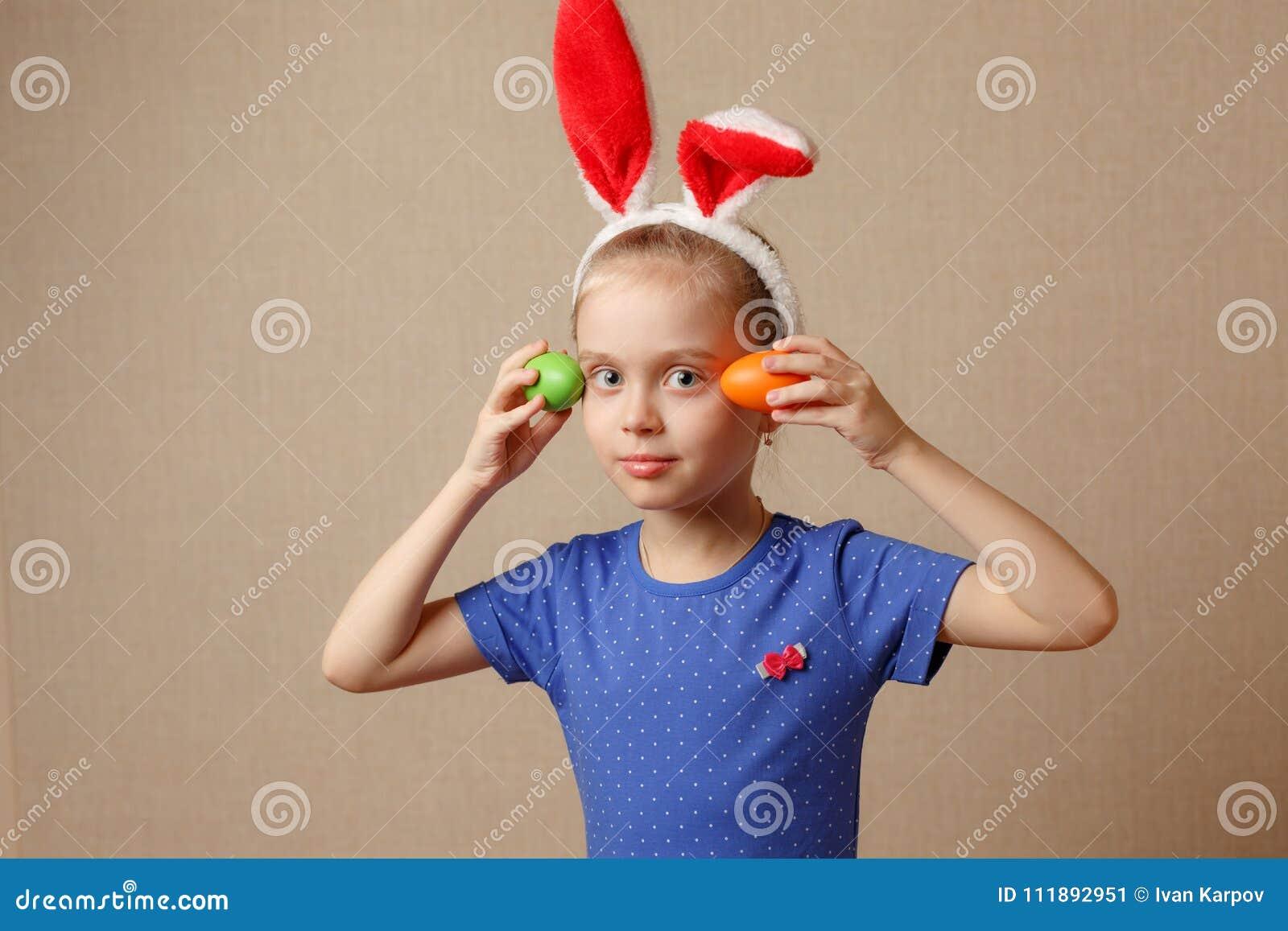 有兔宝宝耳朵和复活节彩蛋的逗人喜爱的小女孩