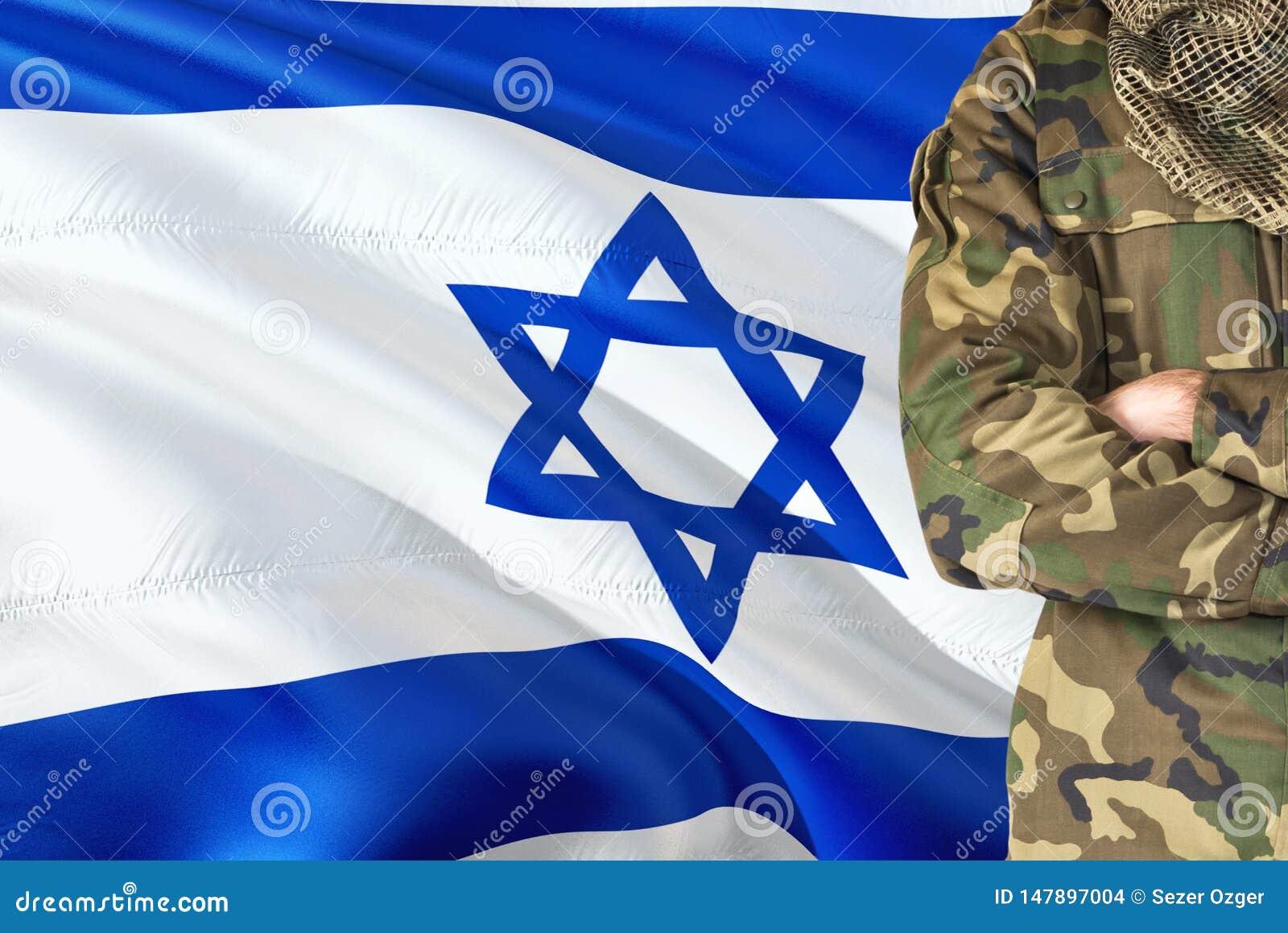 有全国挥动的旗子的横渡的胳膊以军士兵在背景-以色列军事题材