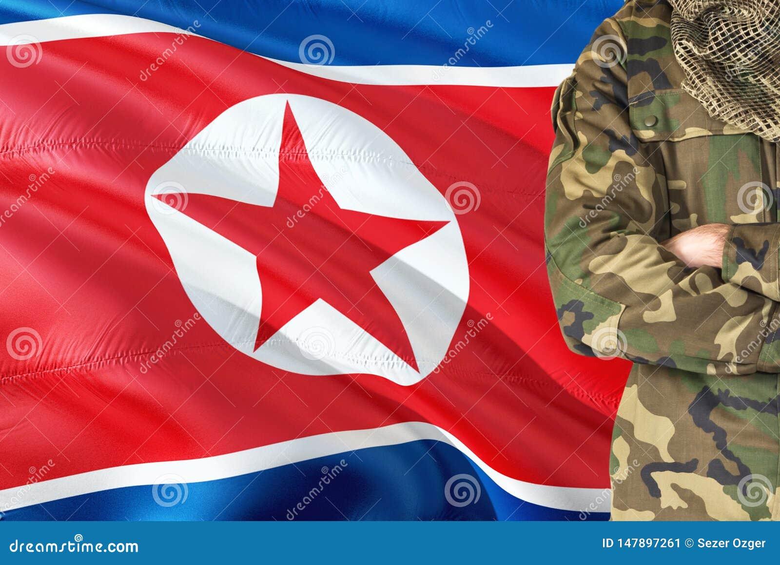 有全国挥动的旗子的横渡的胳膊北朝鲜的士兵在背景-北朝鲜军事题材