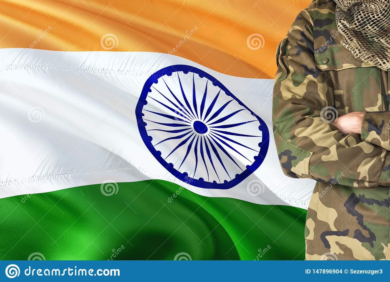 有全国挥动的旗子的横渡的胳膊印度士兵在背景-印度军事题材
