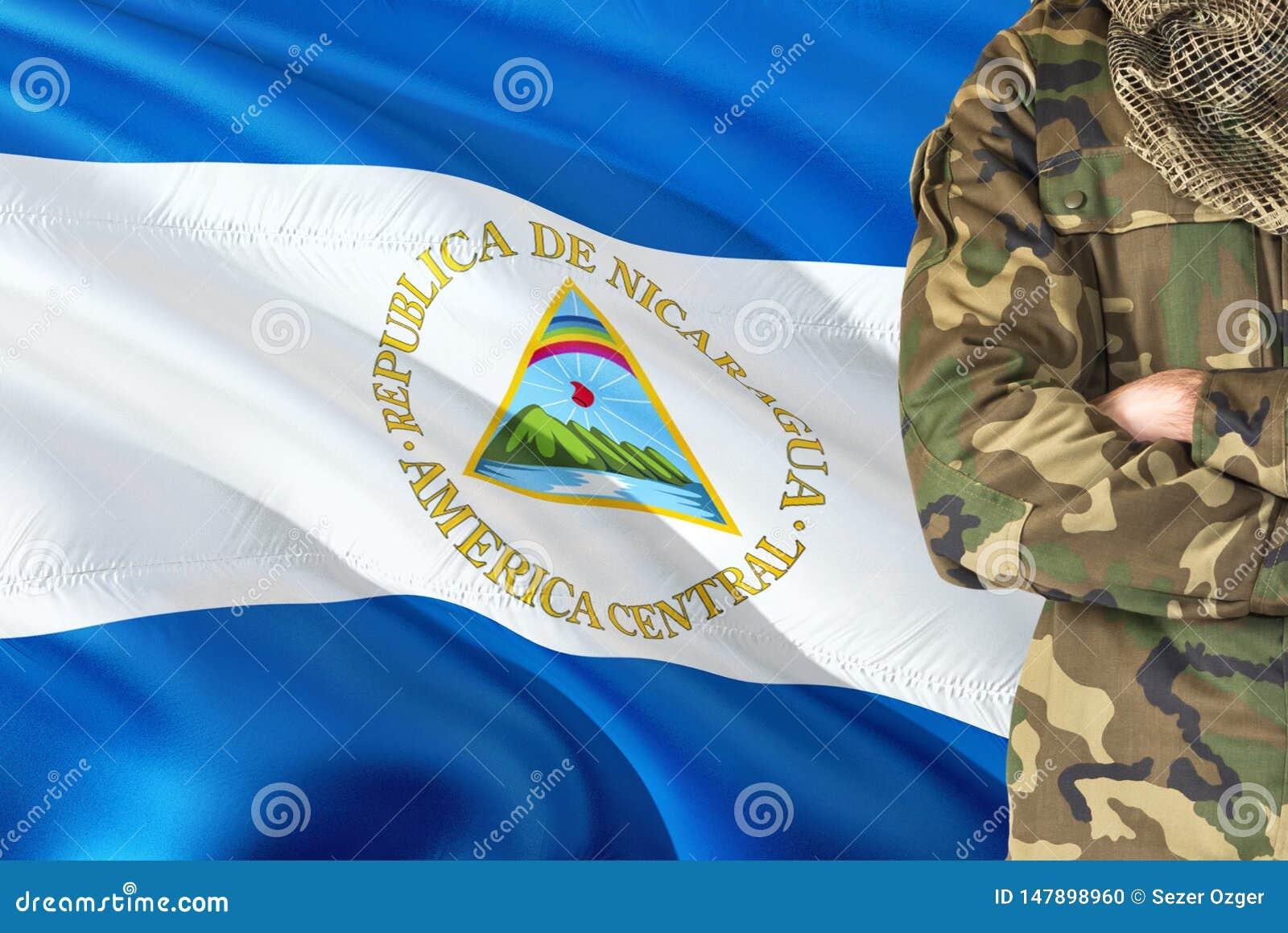 有全国挥动的旗子的横渡的胳膊尼加拉瓜的战士在背景-尼加拉瓜军事题材