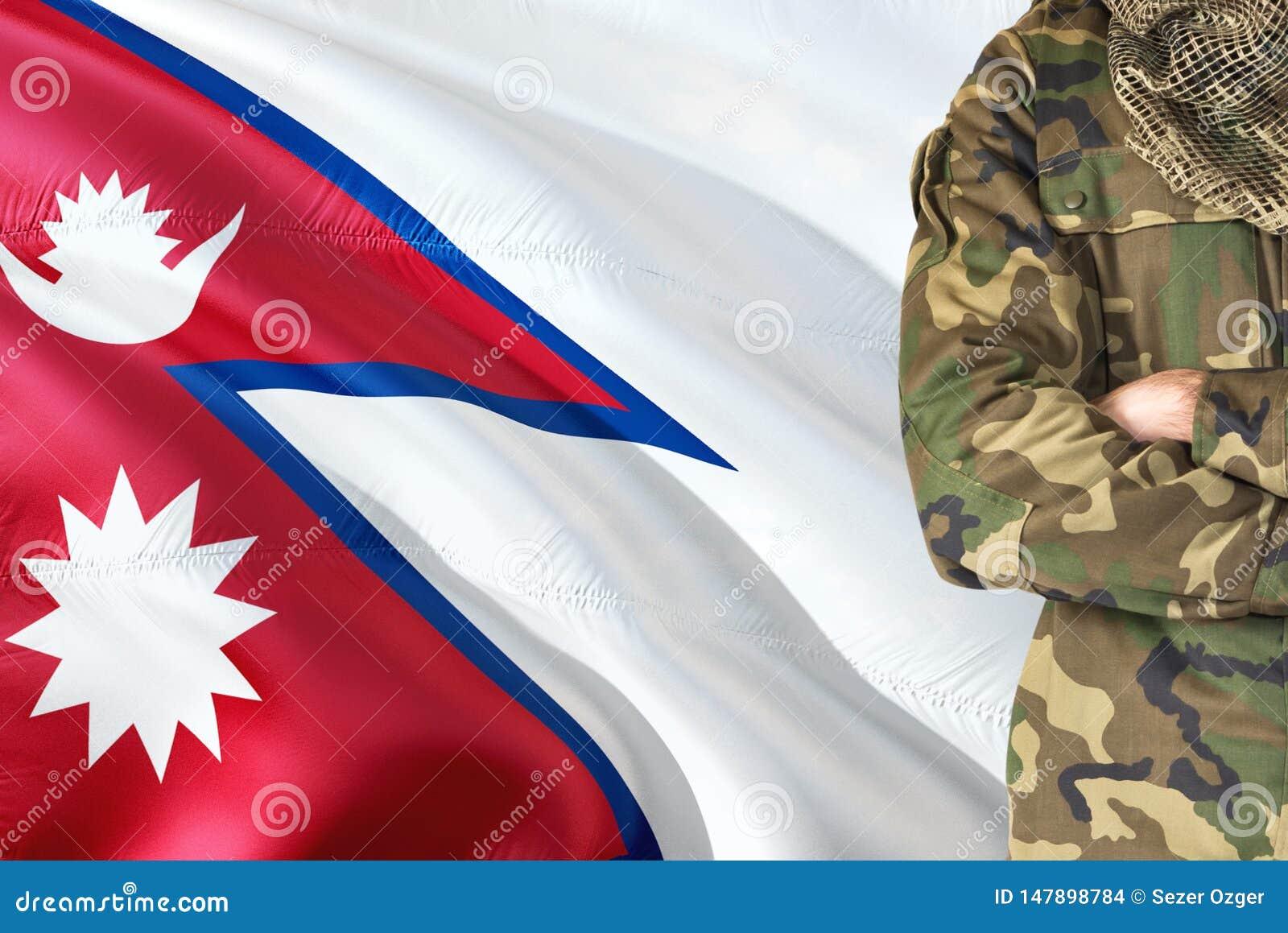 有全国挥动的旗子的横渡的胳膊尼泊尔士兵在背景-尼泊尔军事题材