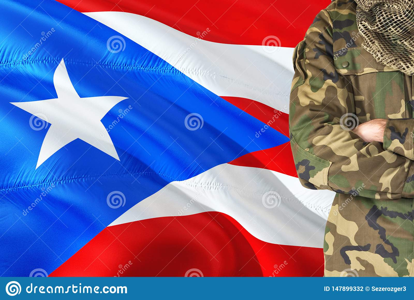 有全国挥动的旗子的横渡的胳膊战士在背景-波多黎各军事题材