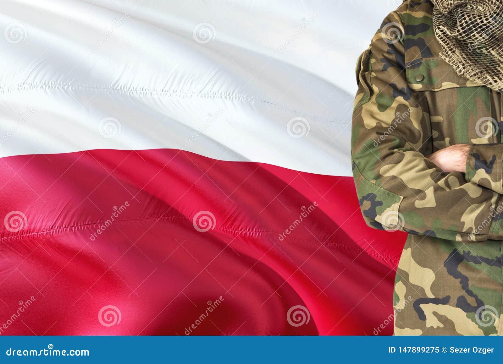 有全国挥动的旗子的横渡的胳膊波兰士兵在背景-波兰军事题材
