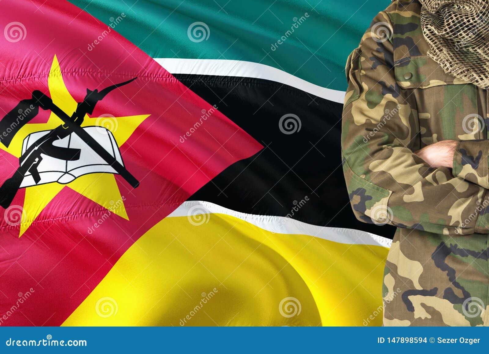 有全国挥动的旗子的横渡的胳膊莫桑比克士兵在背景-莫桑比克军事题材