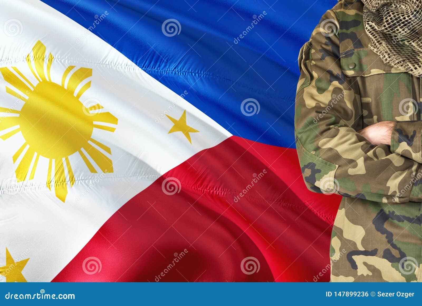 有全国挥动的旗子的横渡的胳膊菲律宾士兵在背景-菲律宾军事题材