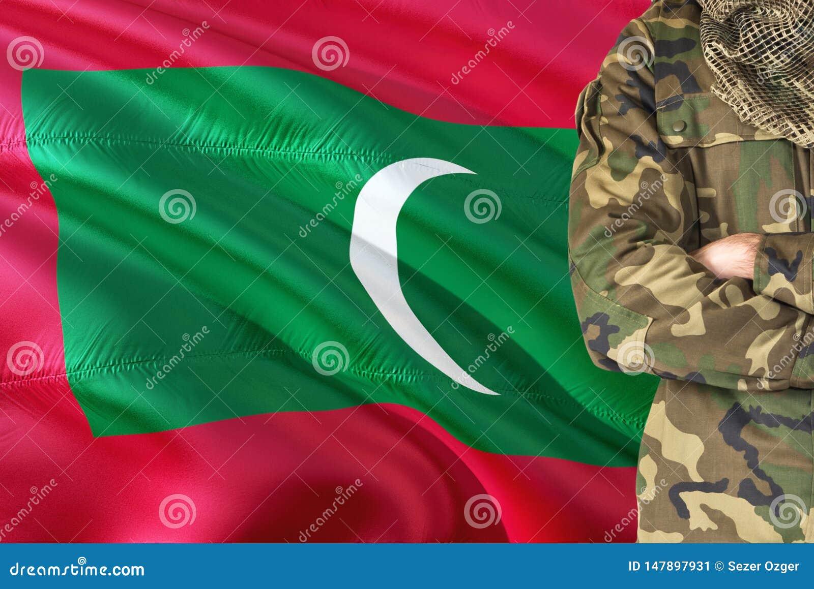 有全国挥动的旗子的横渡的胳膊Maldivan战士在背景-马尔代夫军事题材