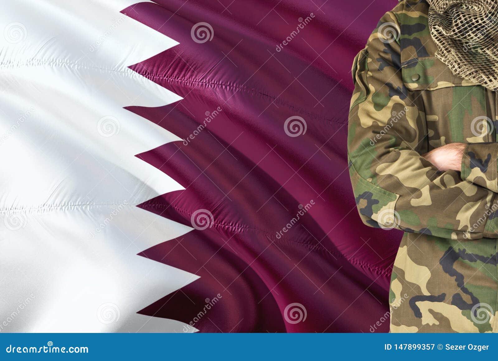 有全国挥动的旗子的横渡的胳膊Qatari战士在背景-卡塔尔军事题材
