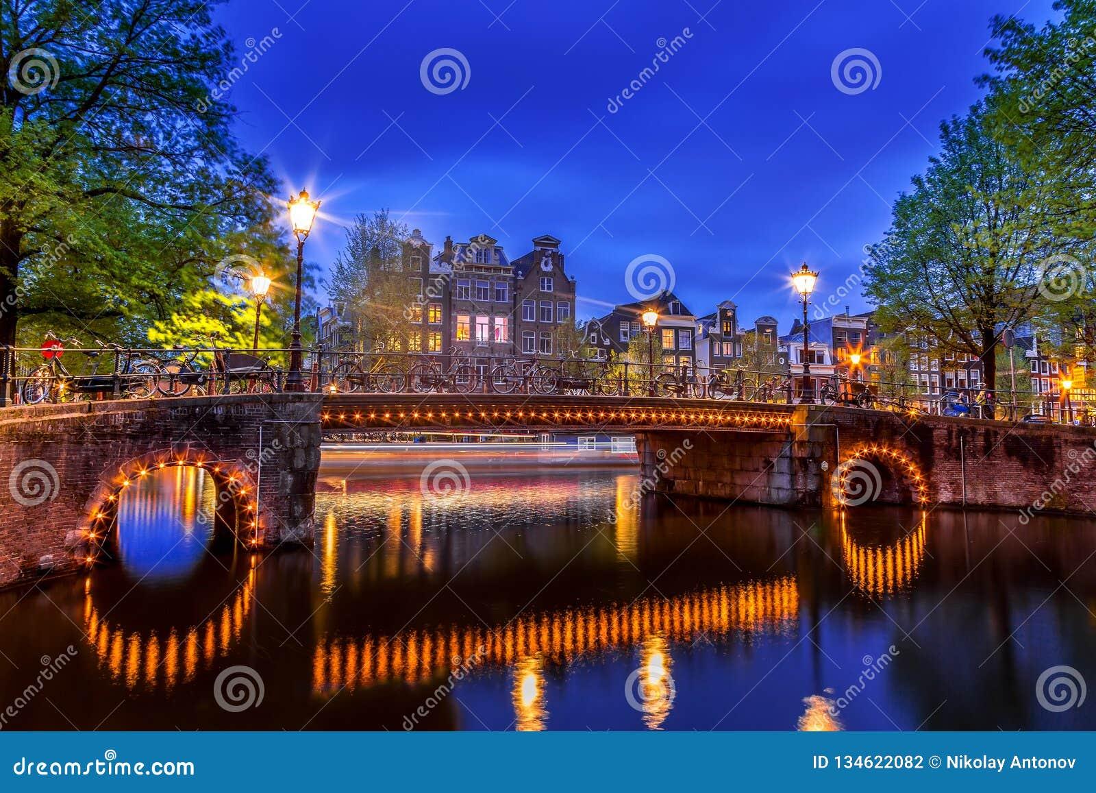 有典型的荷兰房子的阿姆斯特丹运河和有启发性桥梁在暮色蓝色小时在荷兰,荷兰 美丽如画