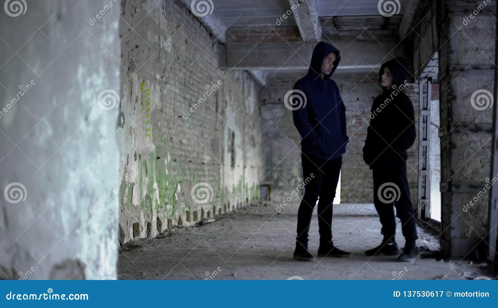 有冠乌鸦的男孩谈话在被破坏的大厦,少年帮会,年轻罪犯