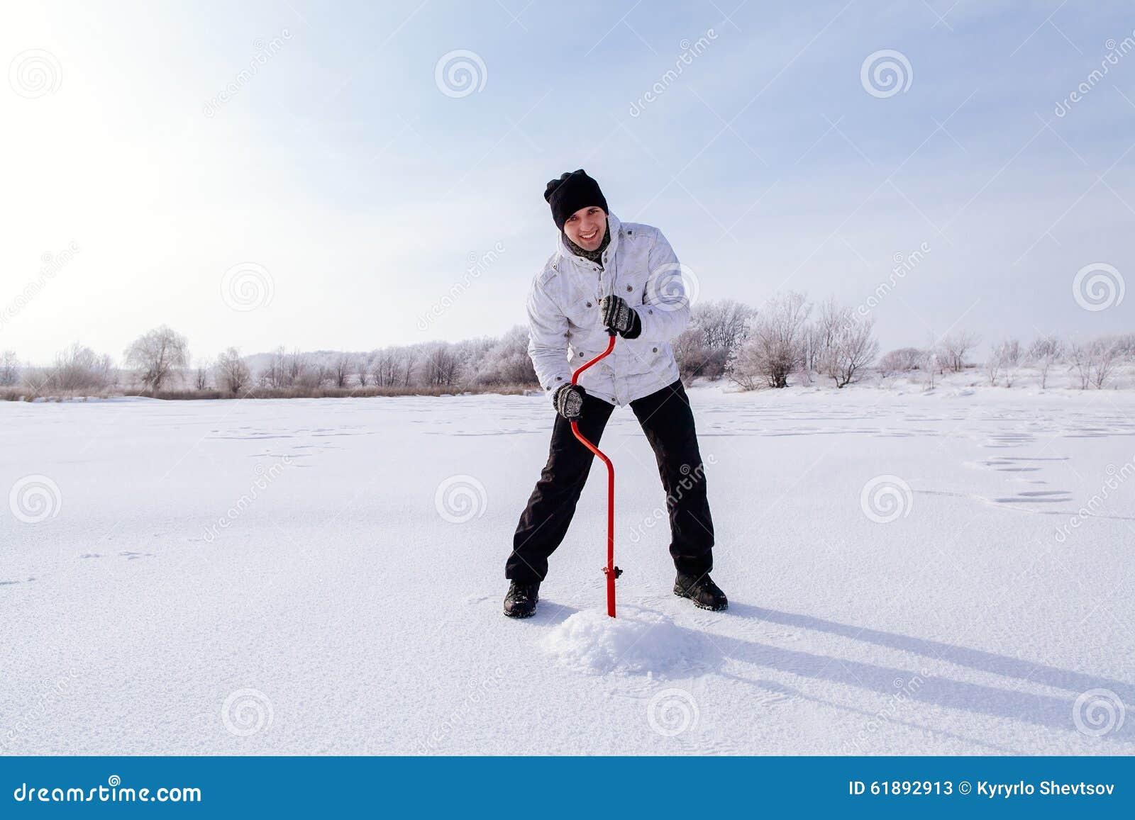 有冰螺丝的冬天渔夫在冻湖