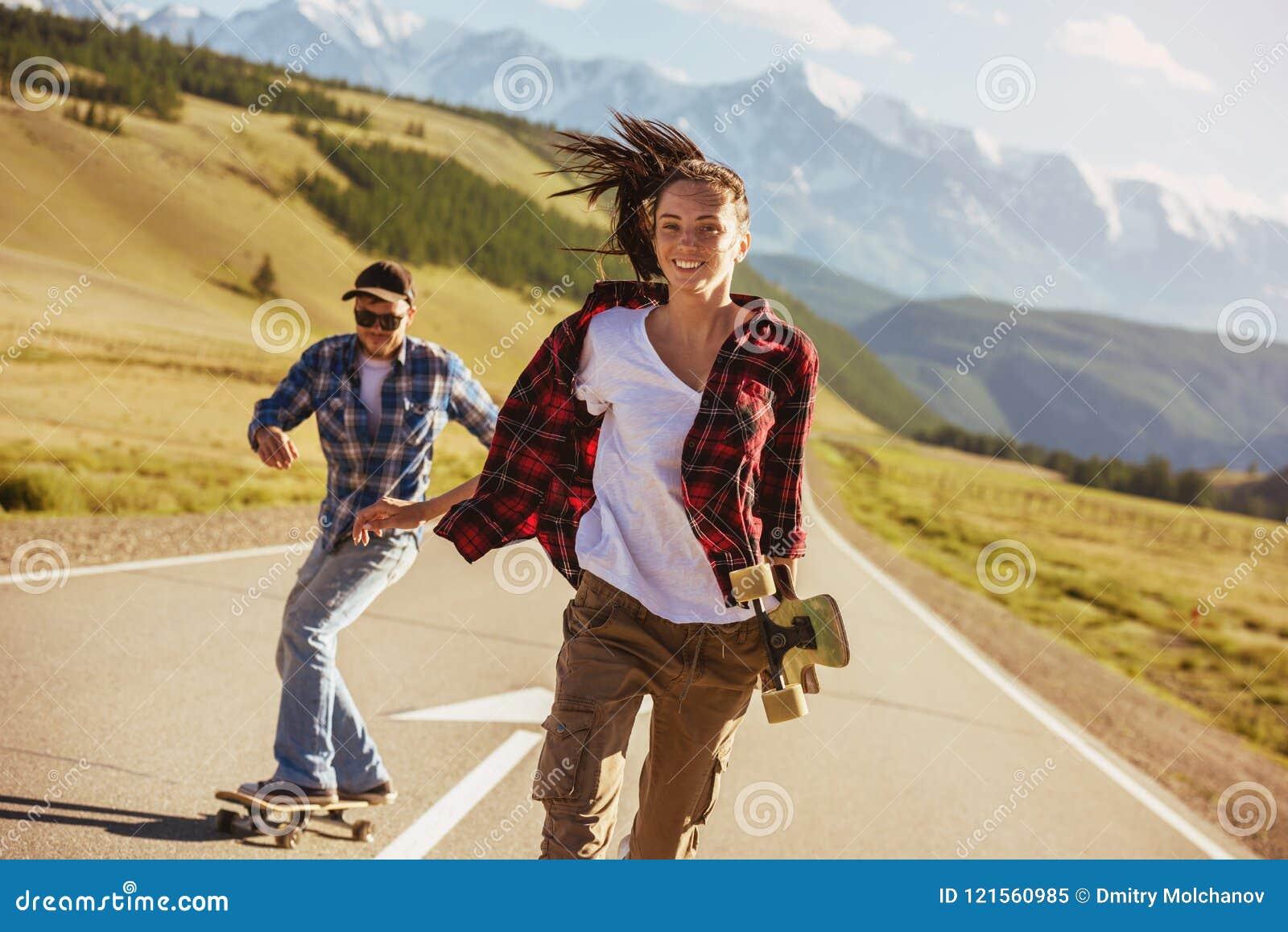 有冰鞋的愉快的在直路的朋友和longboards