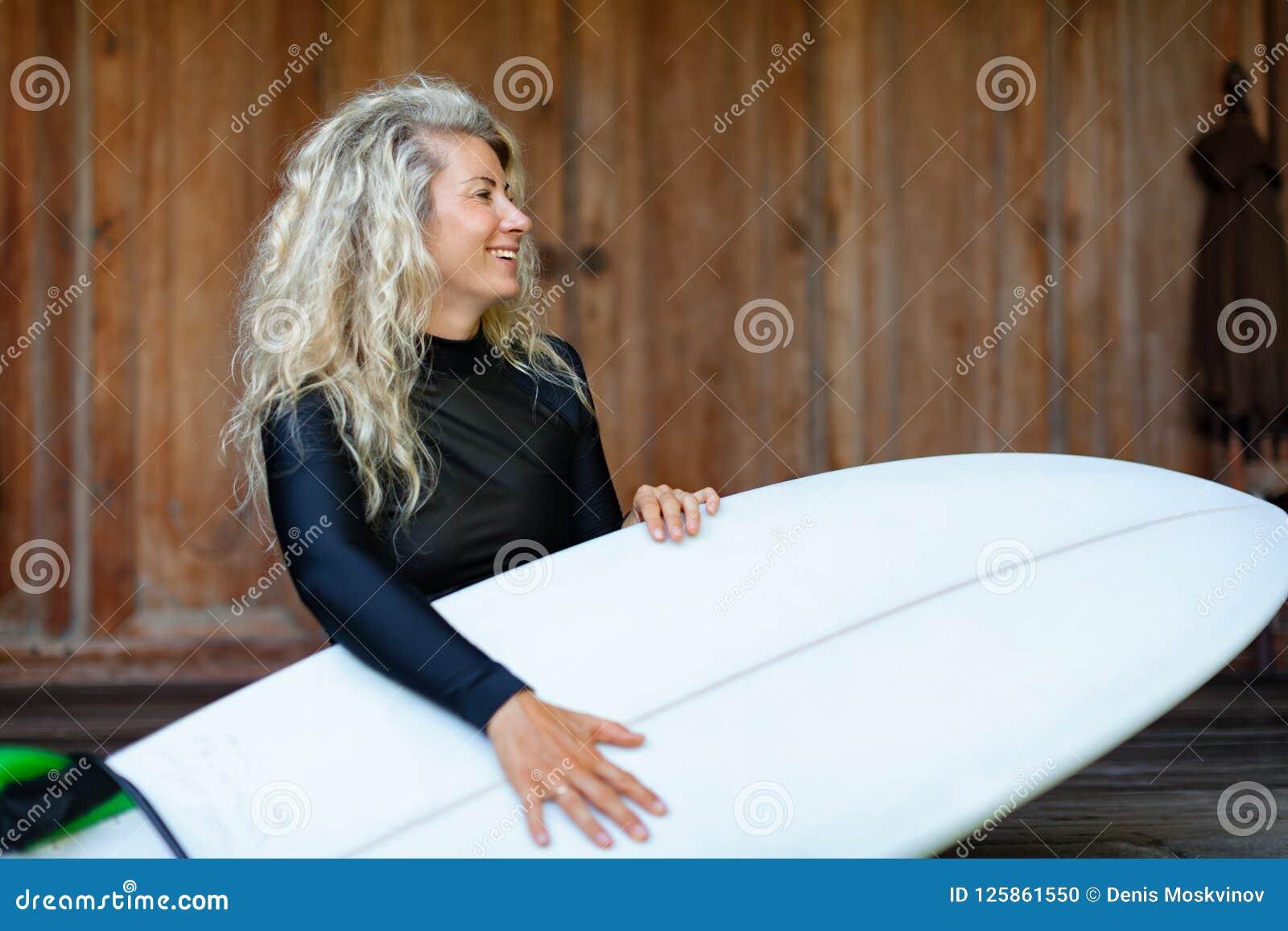 有冲浪板的女孩坐游廊步海滩别墅
