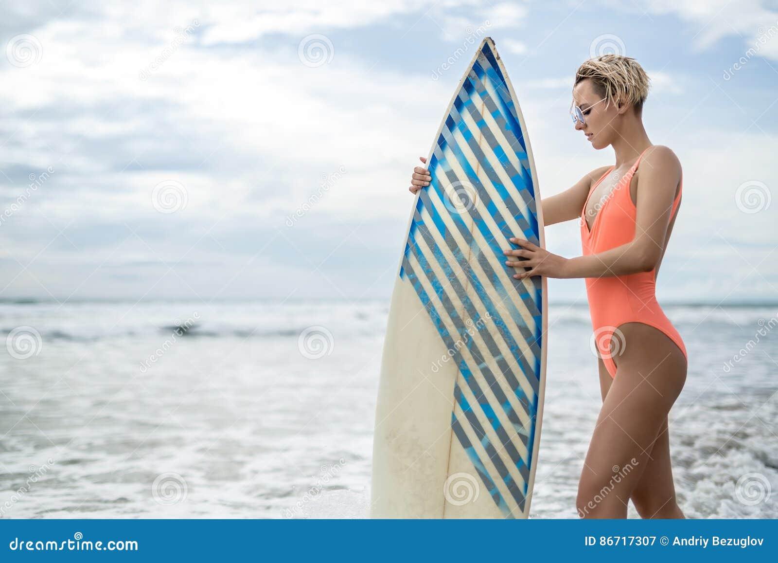 有冲浪板的妇女在海滩