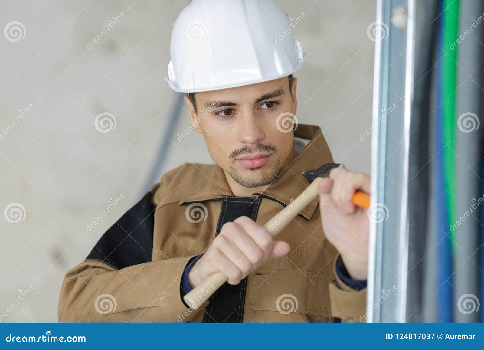 有凿子和锤子的年轻泥工恢复大厦