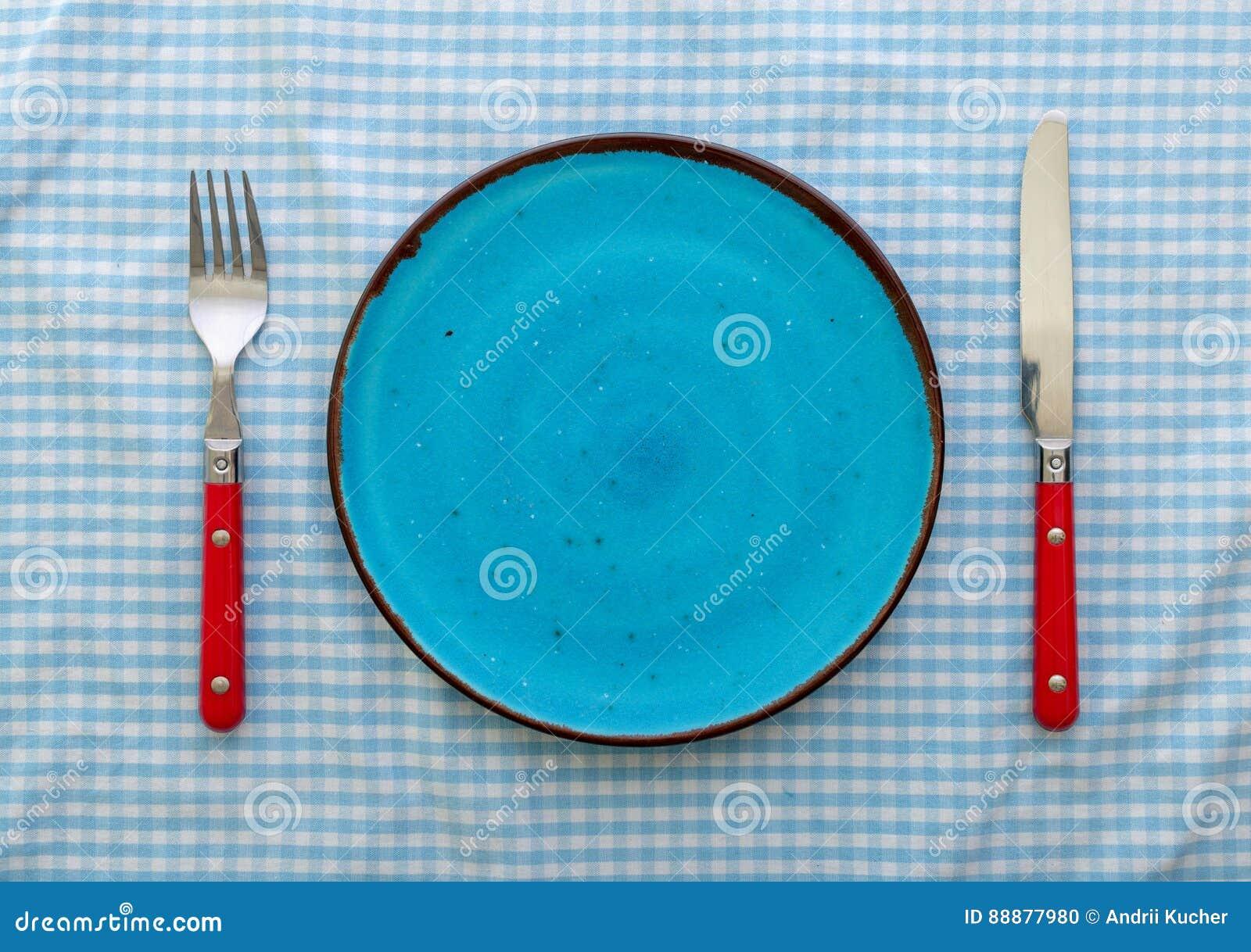 有刀子和叉子的空的蓝色陶瓷板材