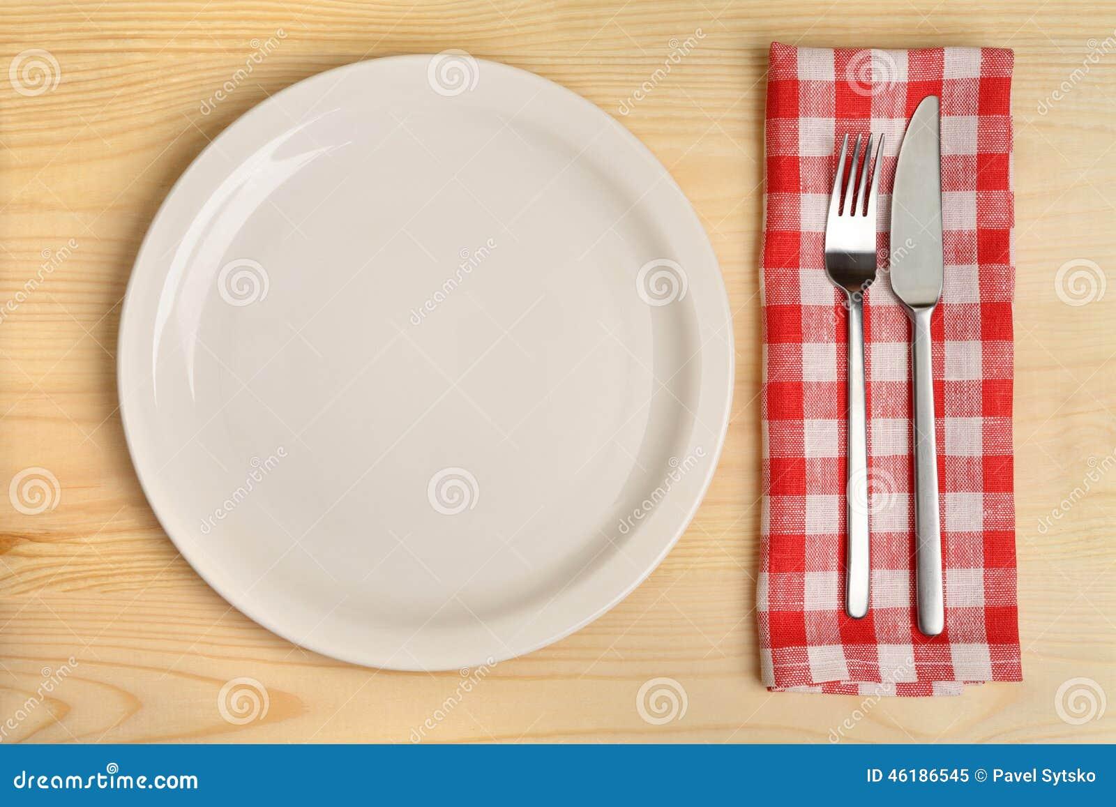 有利器的空的板材在木背景的红色方格的餐巾