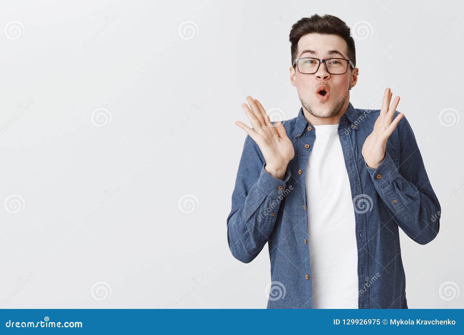 有刺毛的热心愉快和激动的年轻帅哥在举在喜悦的玻璃和蓝色衬衣手,拍手