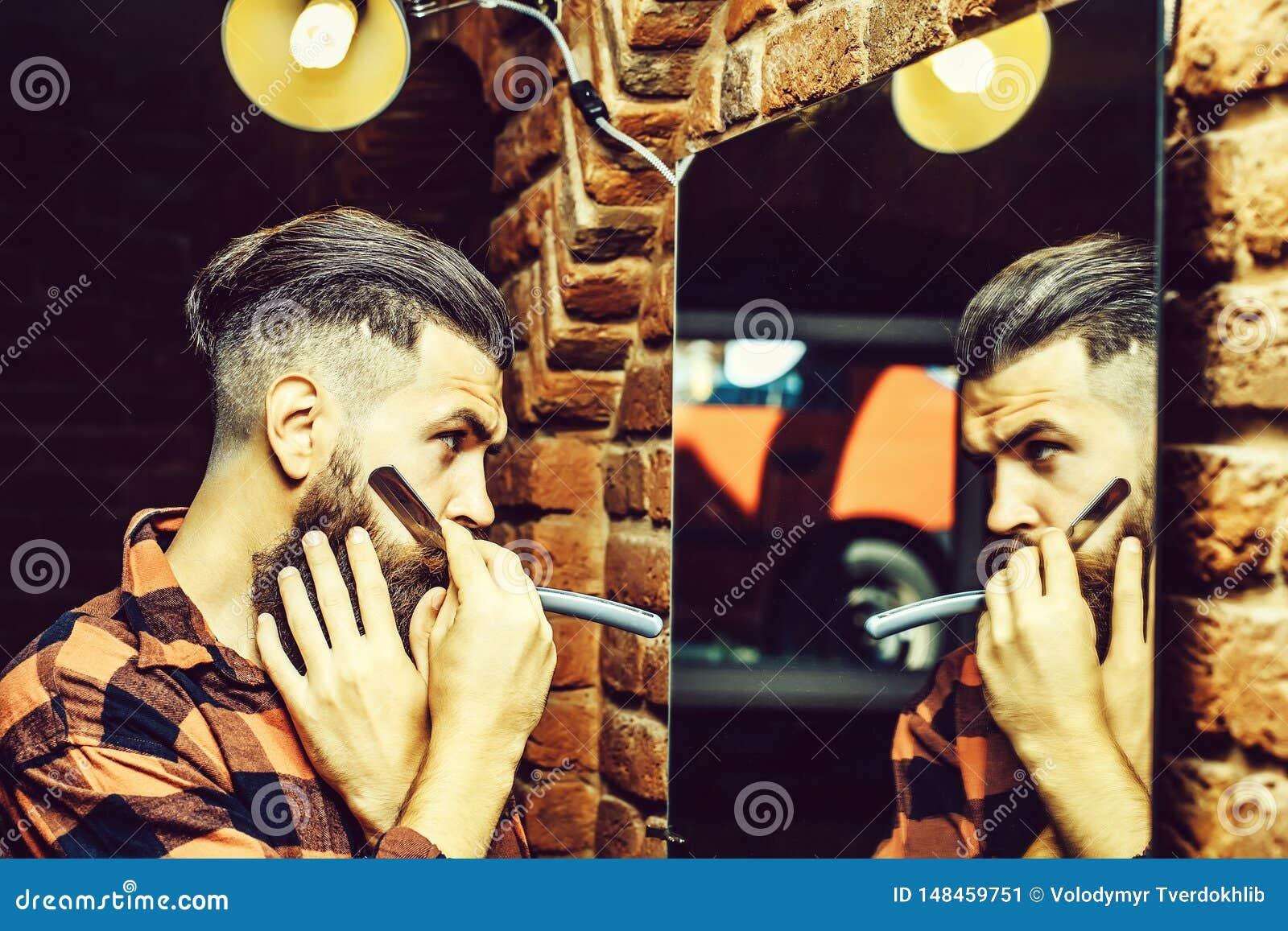 有剃刀的人在镜子附近