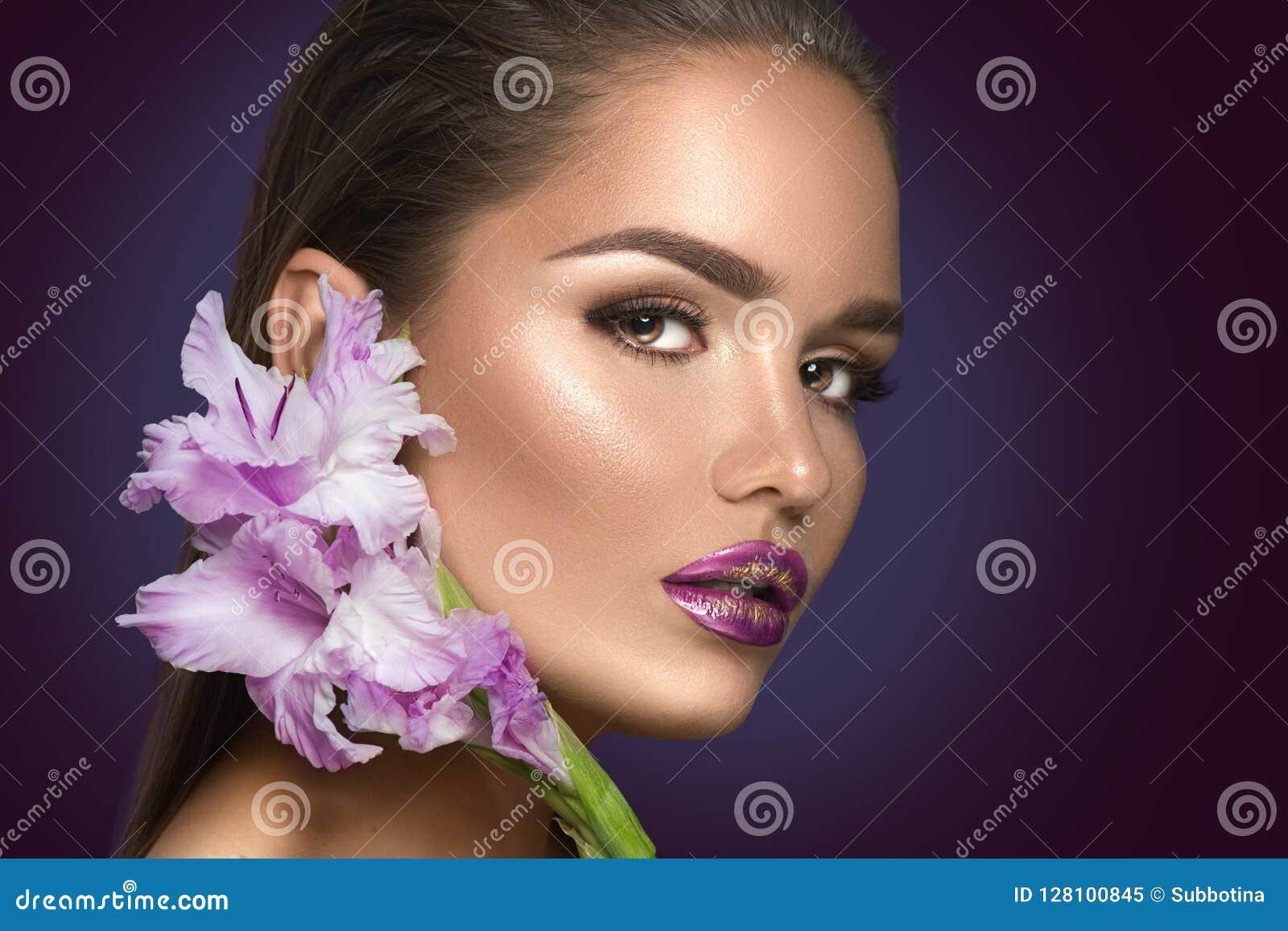 有剑兰花的秀丽时尚深色的女孩 有完善的紫罗兰色时髦构成的魅力性感的妇女
