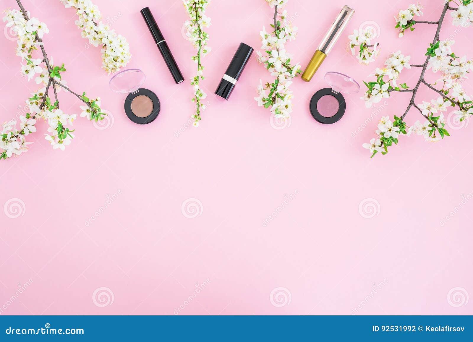 有化妆用品的女性书桌:唇膏、阴影、染睫毛油和白色春天在桃红色背景开花 平的位置,顶视图 秀丽co