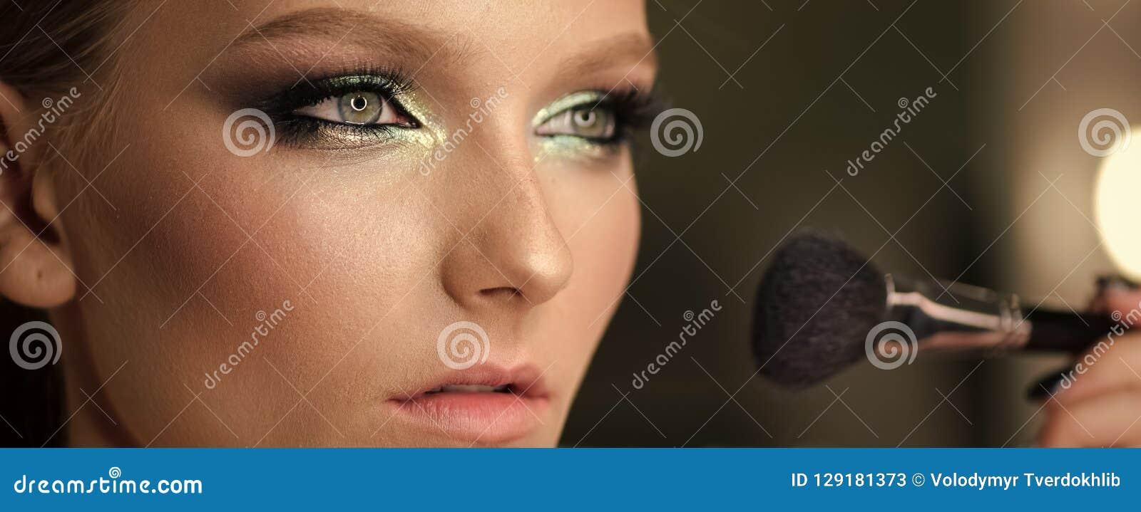 有化妆粉末刷子的美丽的女孩为组成 构成 做申请完善的皮肤