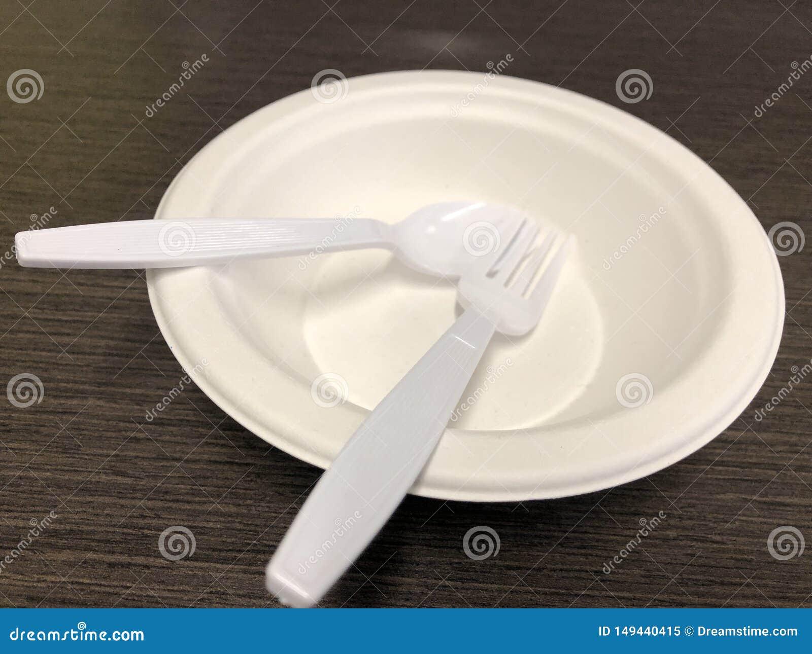 有匙子的白色空的说谎在黑被仿造的早餐桌上的碗和叉子