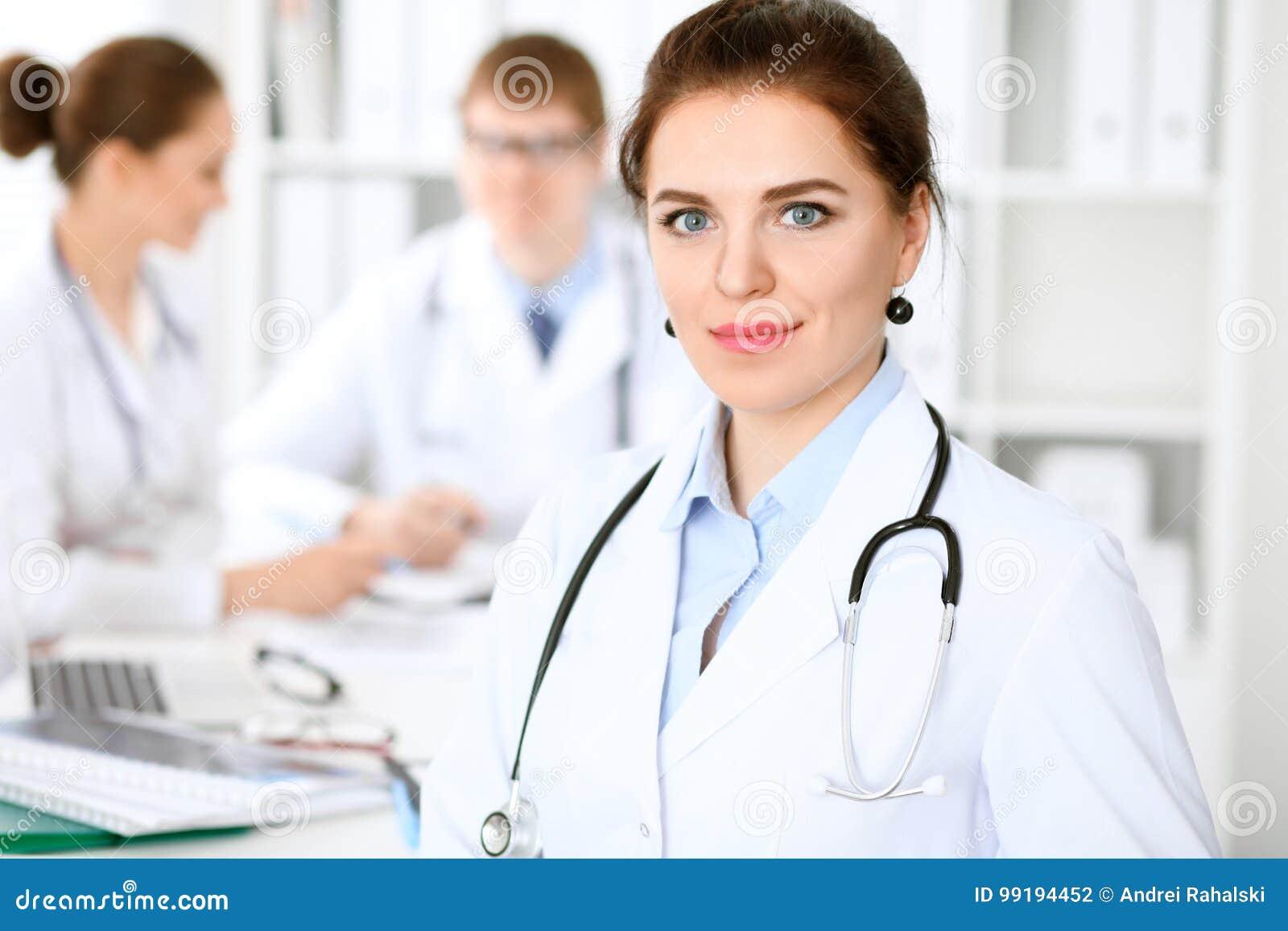 有医护人员的愉快的医生妇女坐在桌上的医院的