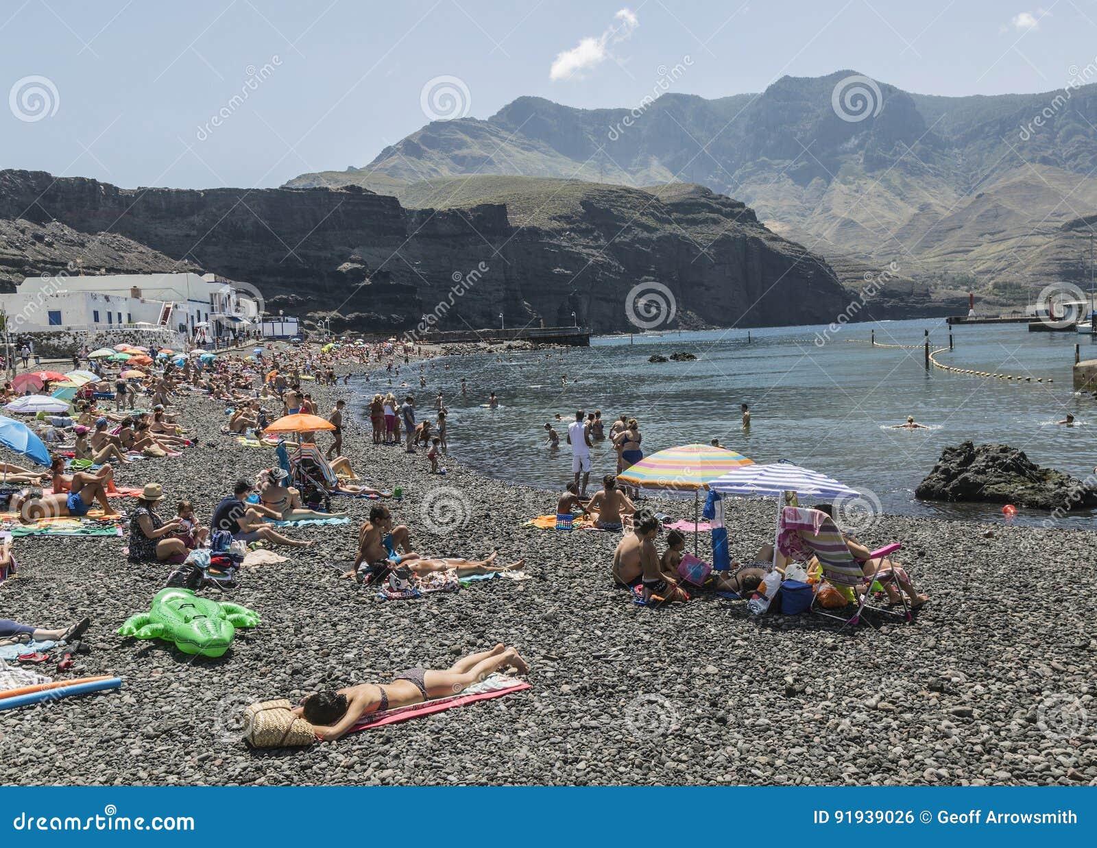有卵石花纹的海滩的游人在Puerto de在大加那利岛的las Nieves,