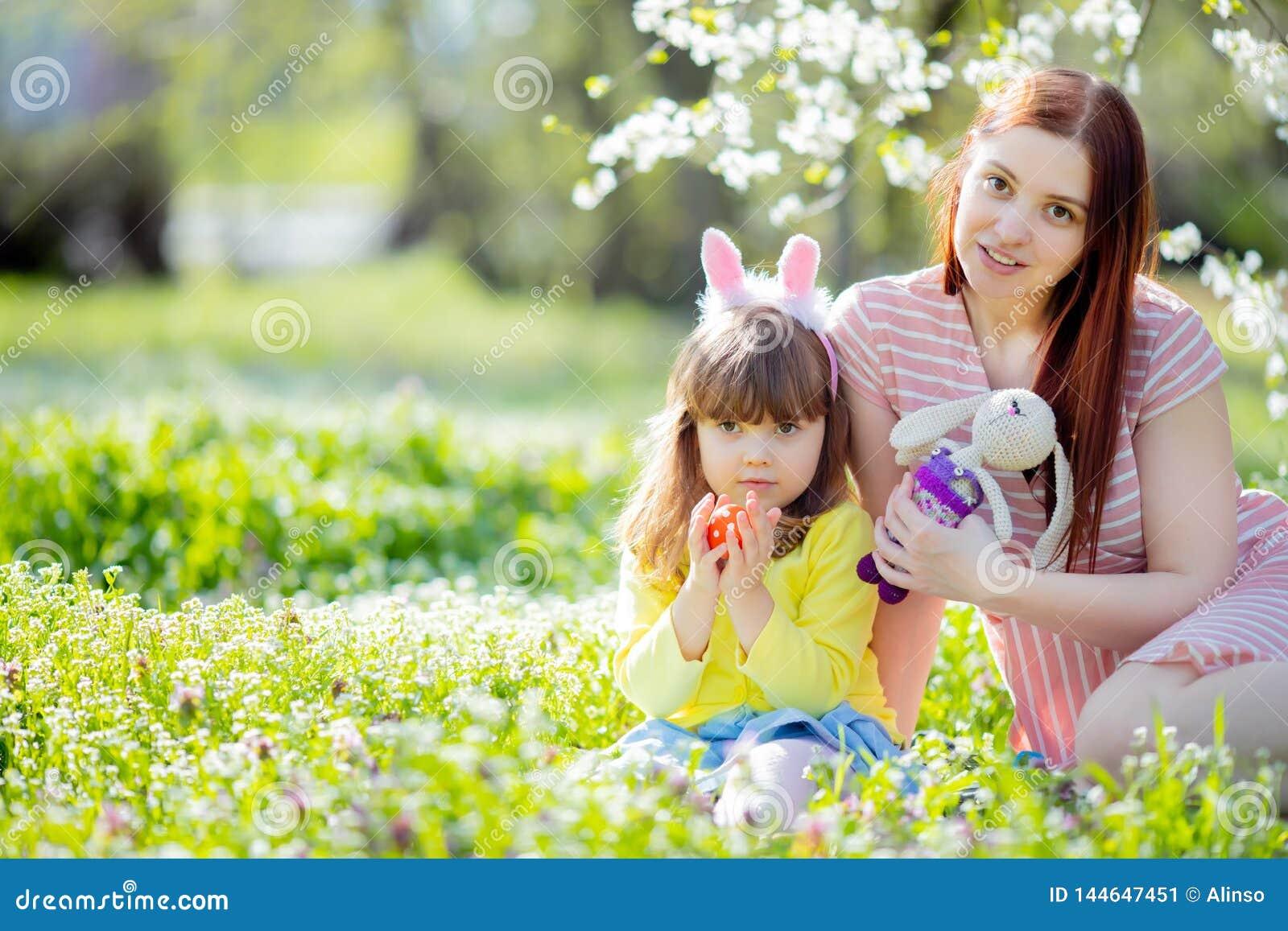 有卷发佩带的兔宝宝耳朵和夏天礼服的逗人喜爱的女孩获得与她的年轻母亲的乐趣,放松在庭院