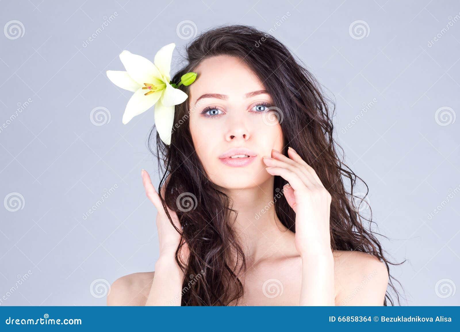 有卷发和百合的妇女在接触她的面颊的头发 夏威夷心情