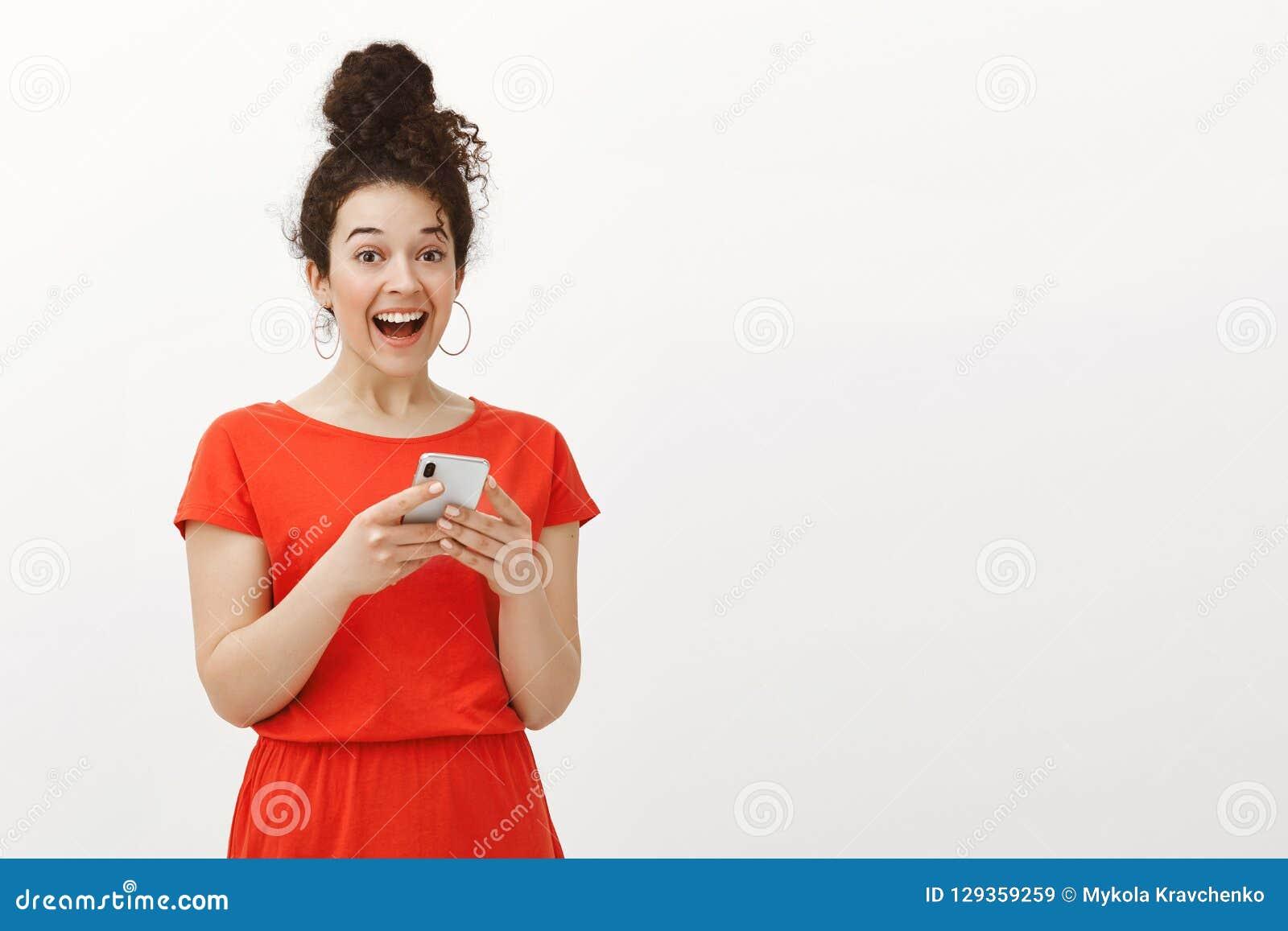 有卷发的在红色礼服,拿着智能手机和大声笑从喜悦的激动的惊奇的愉快的女孩画象