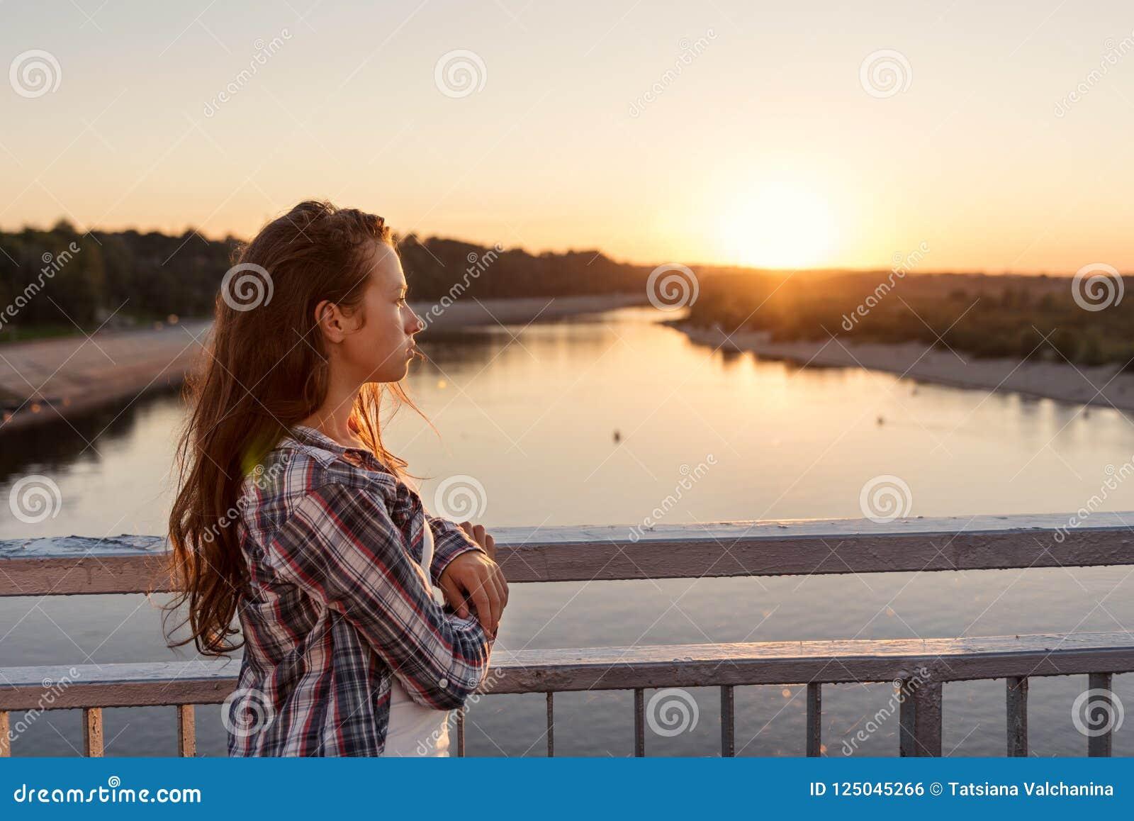 有卷发的少年女孩在生活方式在看日出的桥梁的栏杆附近给身分穿衣
