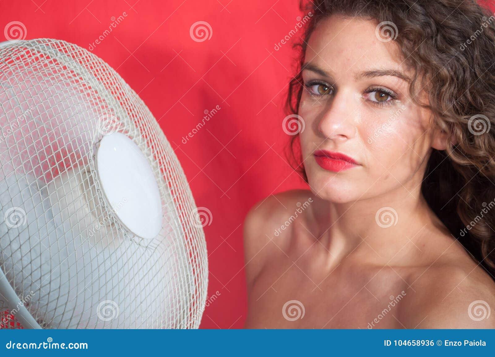 有卷发的性感的深色的女孩有冷却风扇的