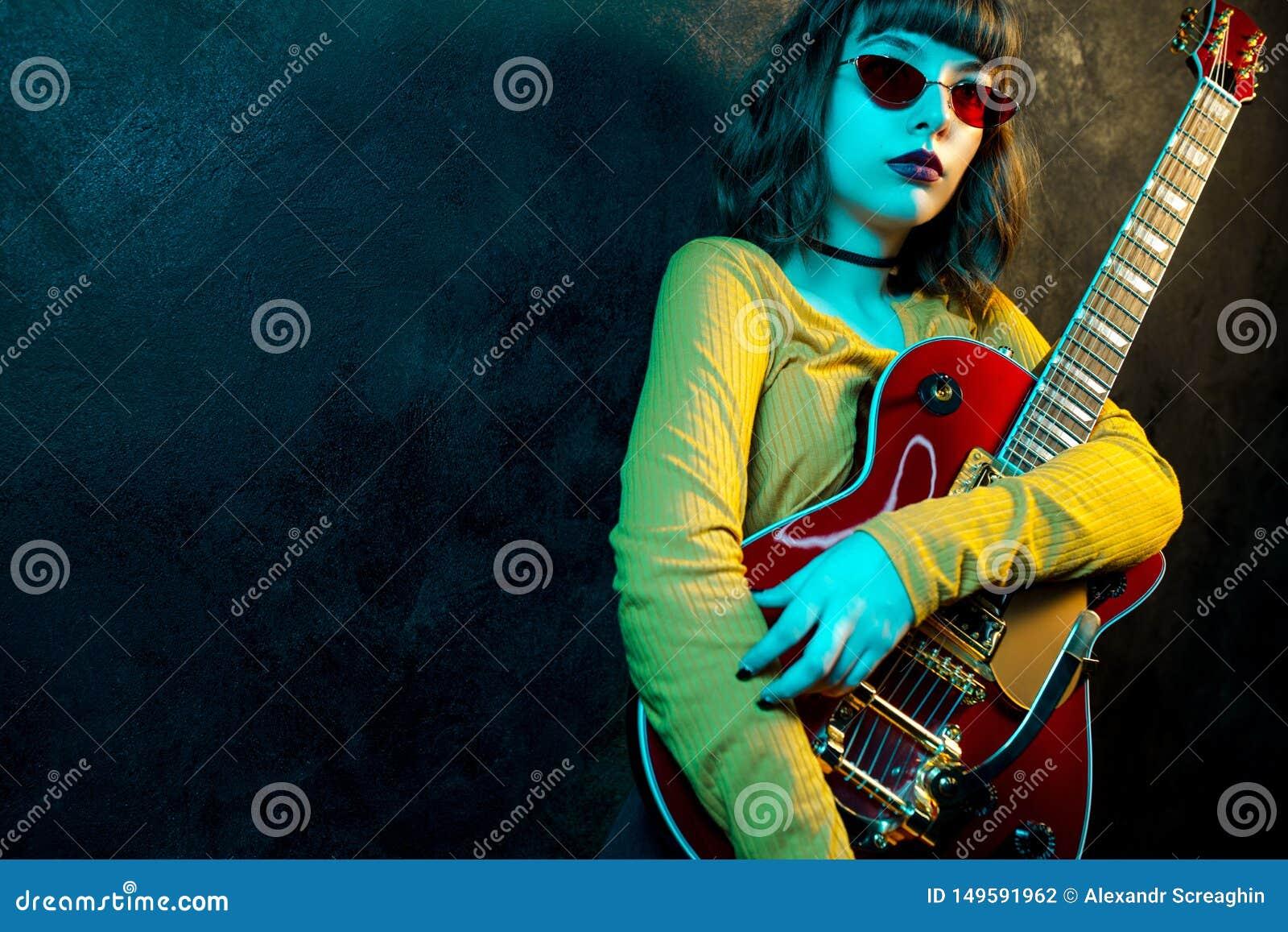 有卷发的时尚年轻行家妇女有在霓虹灯的红色吉他的 岩石音乐家弹电子吉他