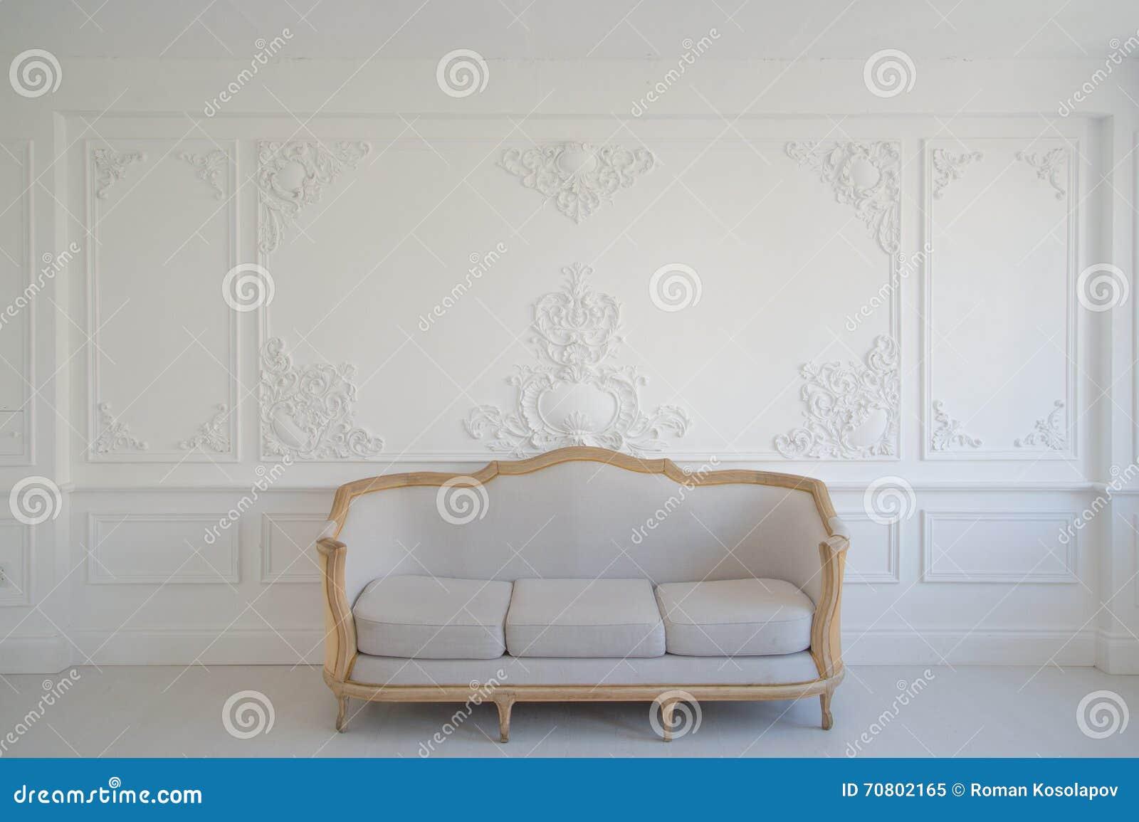 有古色古香的时髦的轻的沙发的客厅在豪华白色墙壁设计浅浮雕灰泥造型roccoco元素