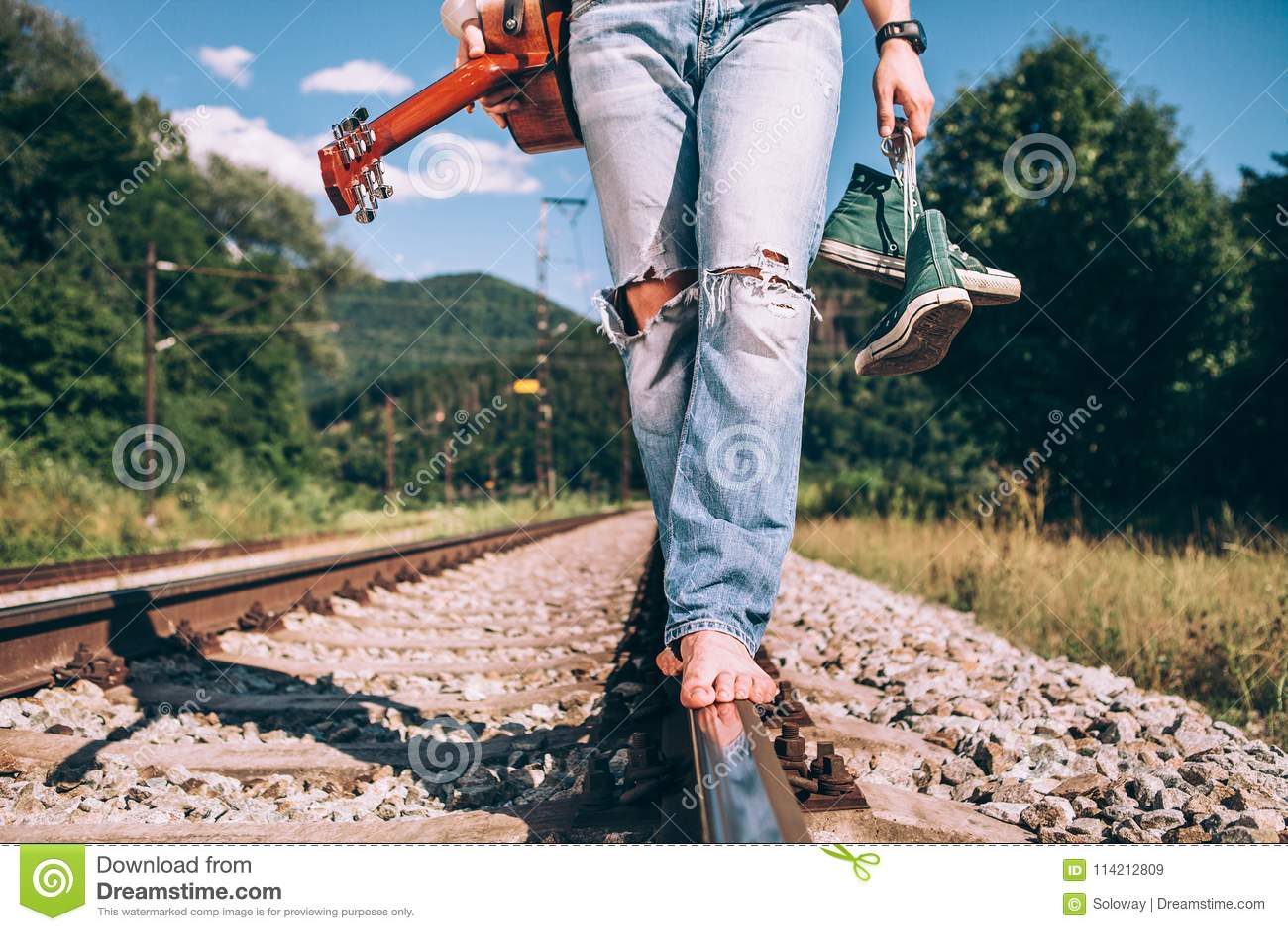 有吉他的年轻人在铁路路,腿图象的关闭走