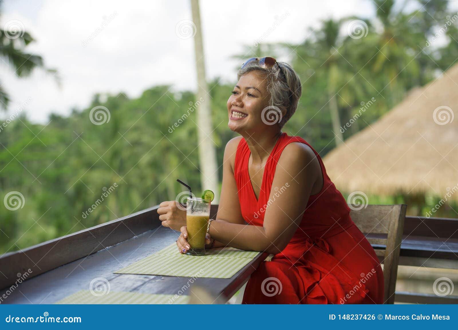 有吸引力和愉快的中部自然生活方式户外画象变老了时髦红色礼服享用的亚裔印度尼西亚妇女