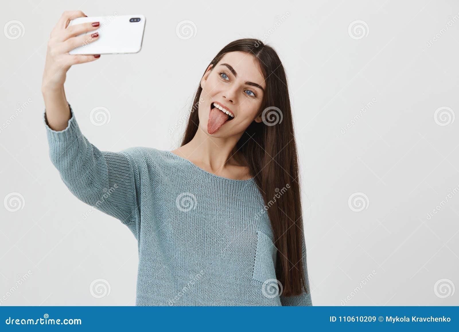 有吸引力和时髦深色的上升的手,当采取在智能手机的selfie,伸出舌头和做逗人喜爱的面孔时