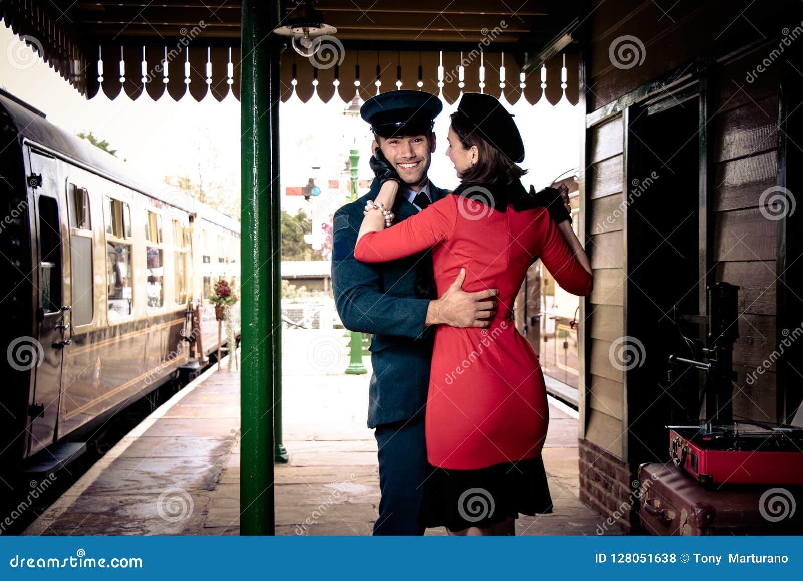 有吸引力的夫妇在有便携式的电唱机的火车站平台跳舞