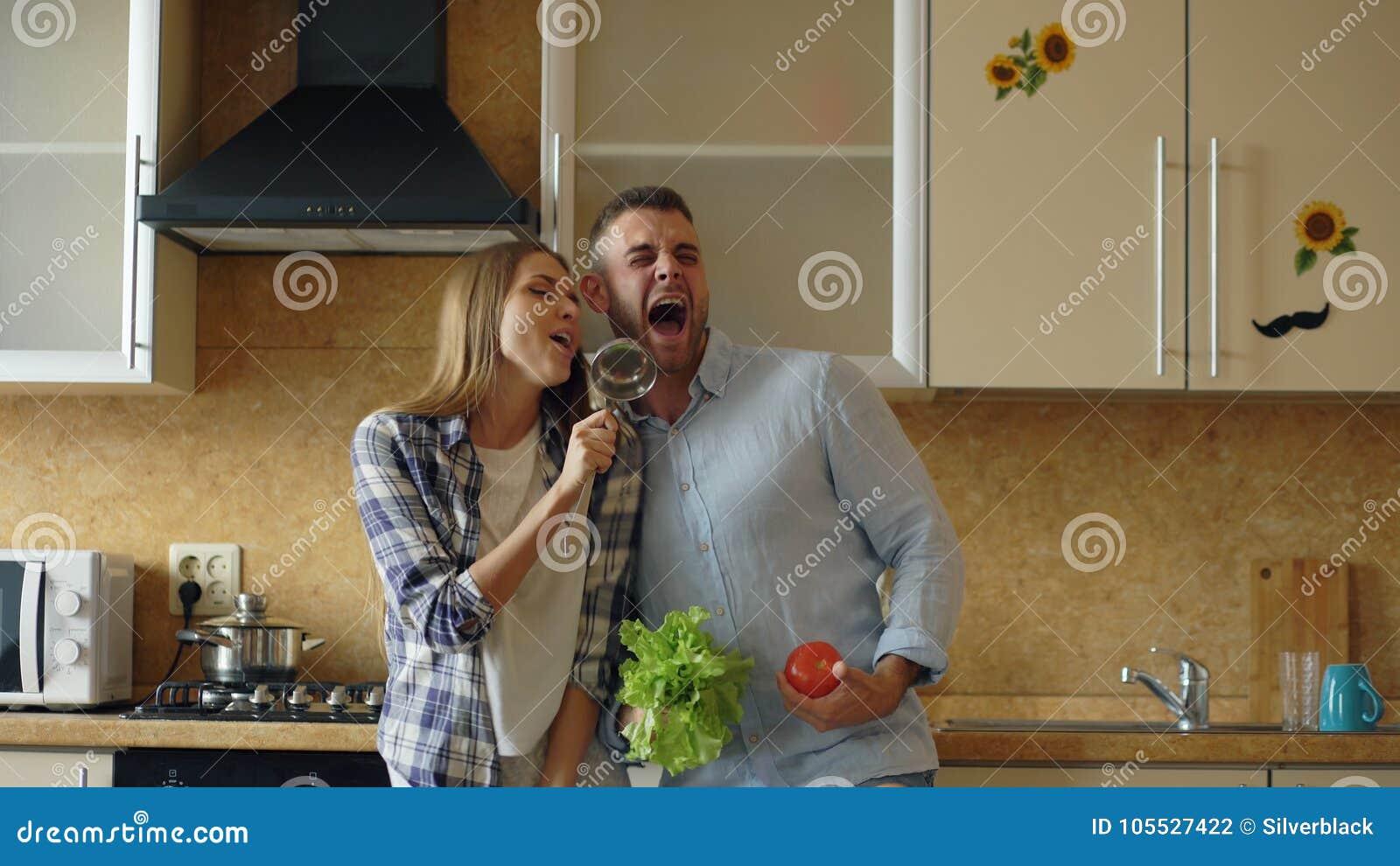 有吸引力的年轻快乐的夫妇有乐趣跳舞和唱歌,当在家时烹调在厨房