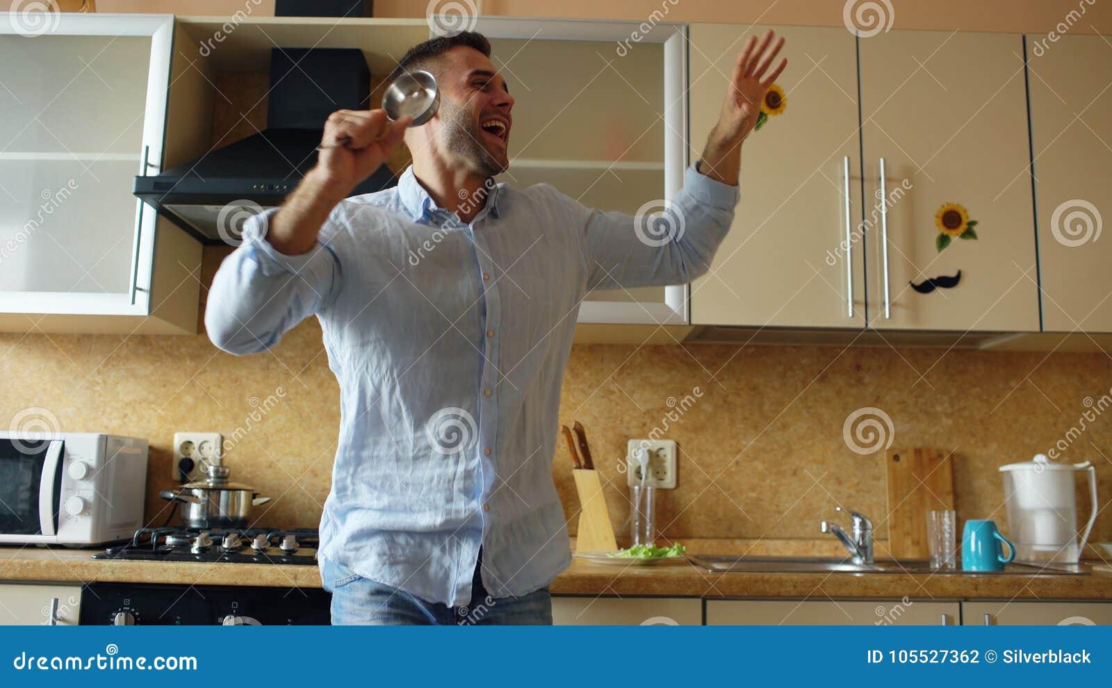 有吸引力的年轻滑稽的人跳舞和唱歌与杓子,当在家时烹调在厨房里